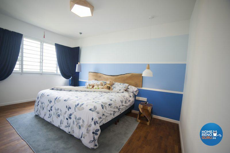 The cool, clean bedroom sports a feature wall in bands of blue