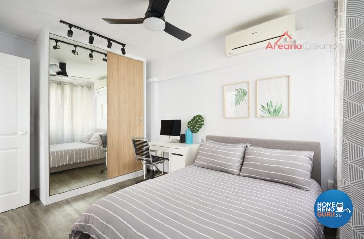 Bed with grey bedsheets and white stripes, ceiling fan, brown wardrobe with full length mirror and study table