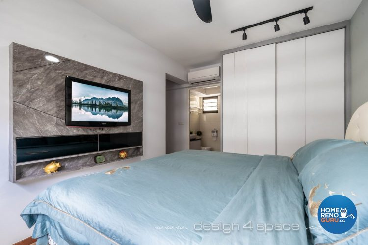 Bedroom with bed with blue bedsheets, white wardrobe and wall-mounted TV