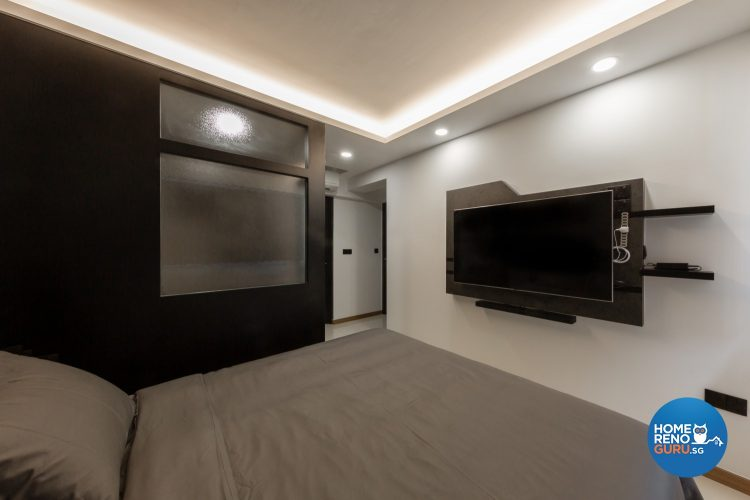Grey bed, wall-mounted TV and black wall with frosted glass