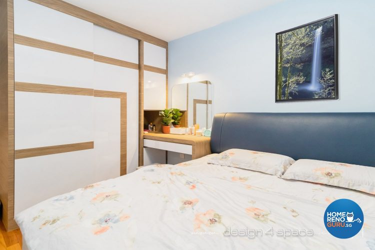 Bed with floral bedsheets, blue headboard and white wardrobe with brown lines