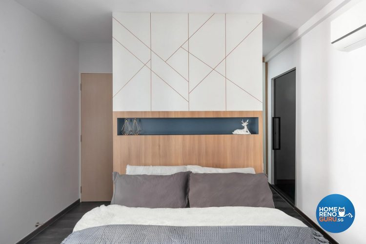 Bed with brown headboard and wall with intersecting lines