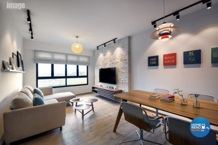 Brick feature wall behind the tv, round hanging lamp, sofa and dining table and chairs