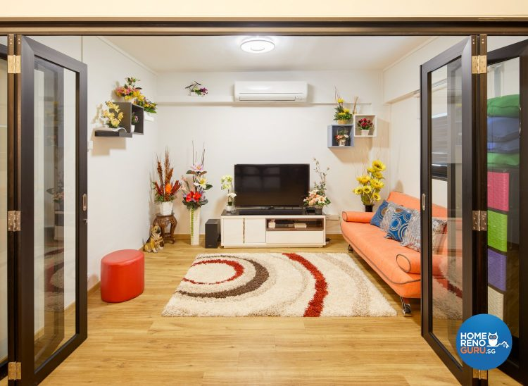 Rug with circle patterns, orange sofa, red stool and tv