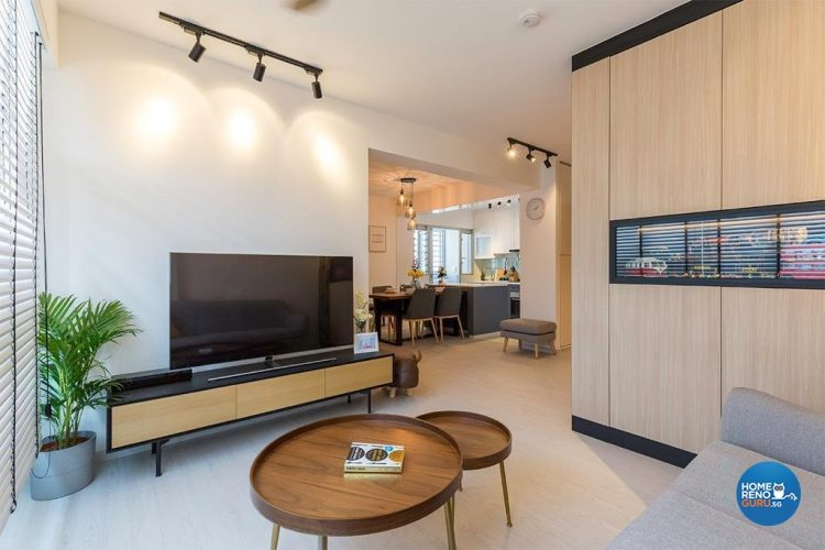 Circular, wooden coffee table, tv on tv console and brown wall