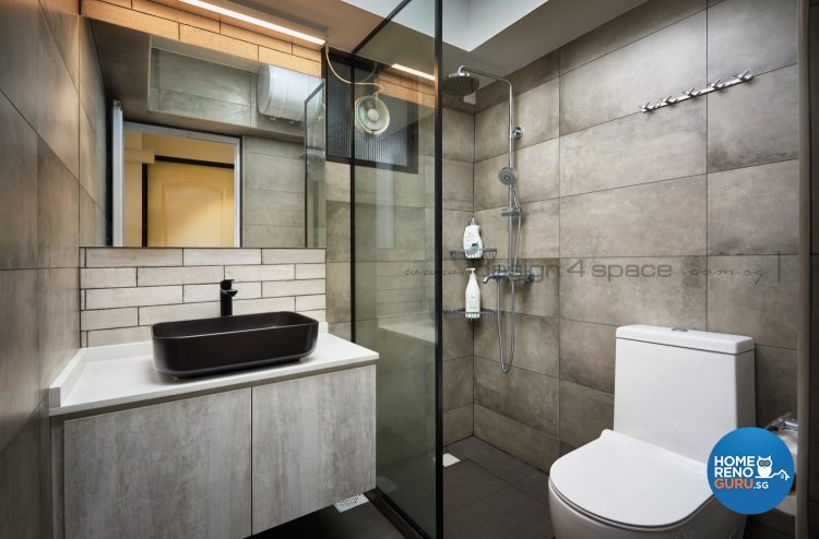 Black sink, white toilet bowl and glass partition