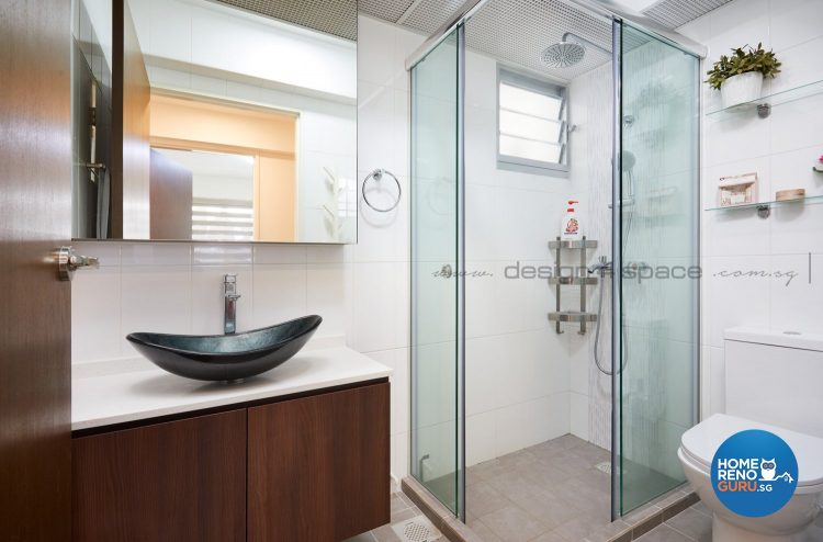 Black sink with rounded edges, brown cabinets and standing shower