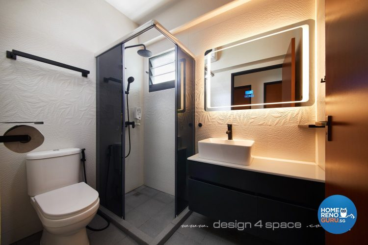 Standing shower with black tinted glass, white toilet bowl and mirror with lights