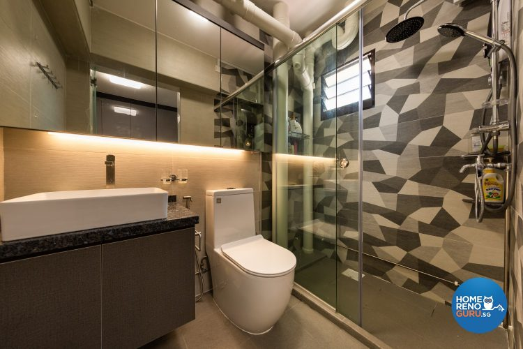 Geometric feature wall, white toilet bowl and glass partitions