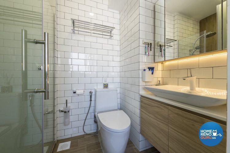 White tiled walls, white toilet bowl, white sink and brown shelves