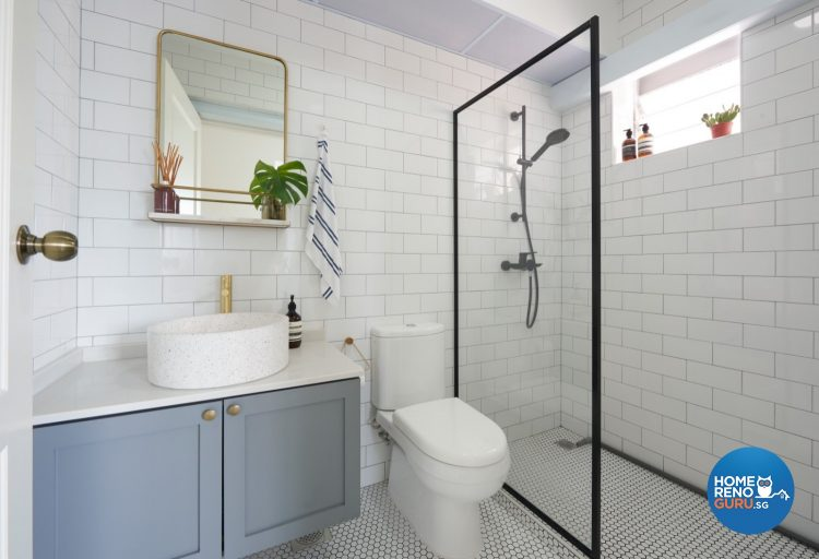 White-tiled bathroom with glass shower partition