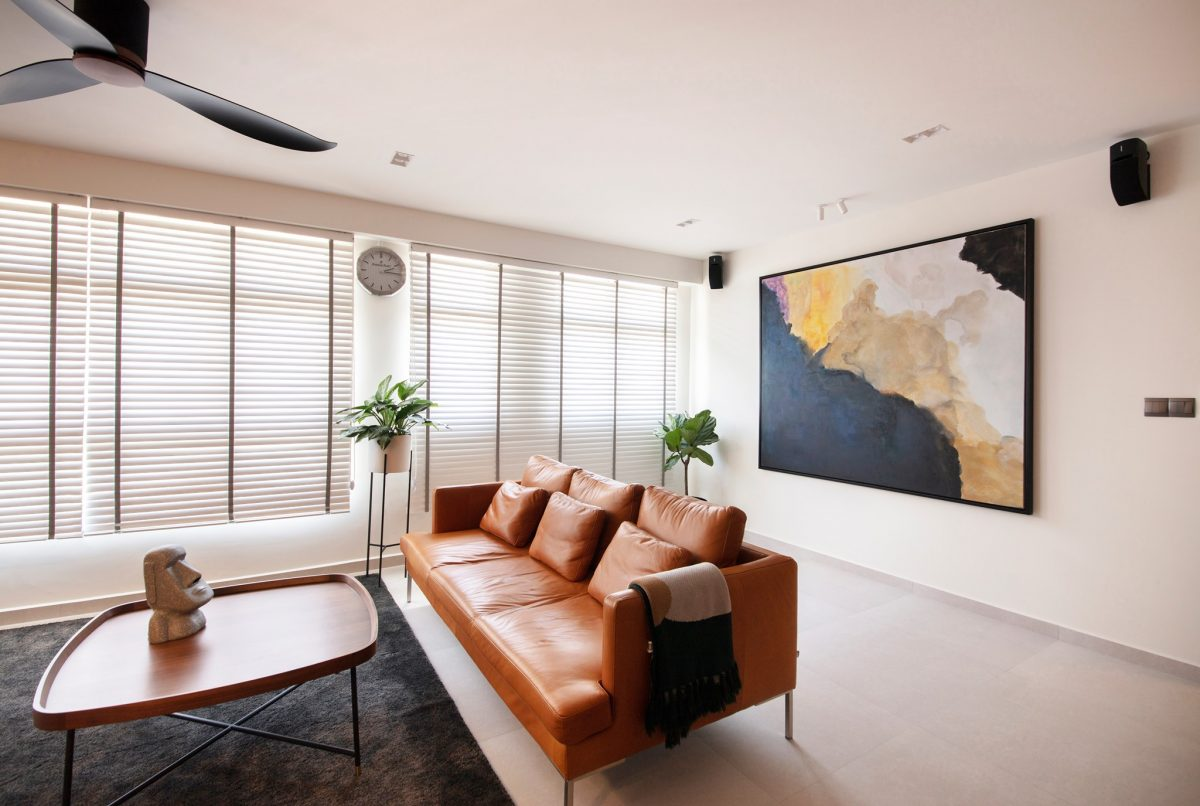 Living room with a brown leather sofa and painting