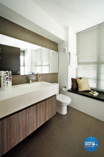 A toilet installed with large windows and blinders, bathed in natural light