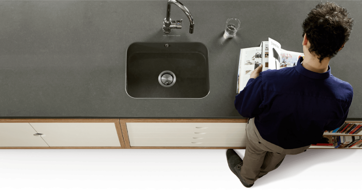 Man reading magazine at a Quartz kitchen countertop