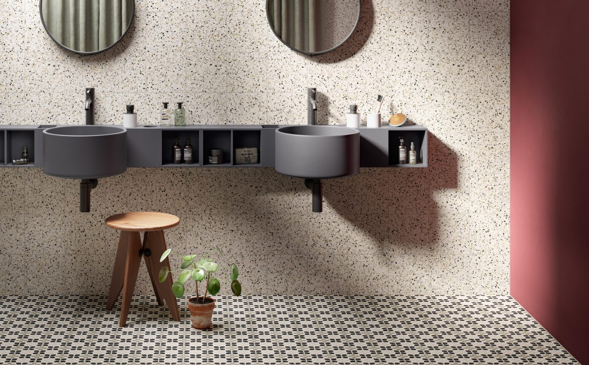 Toilet with 2 mirrors, sinks, and tiled floor