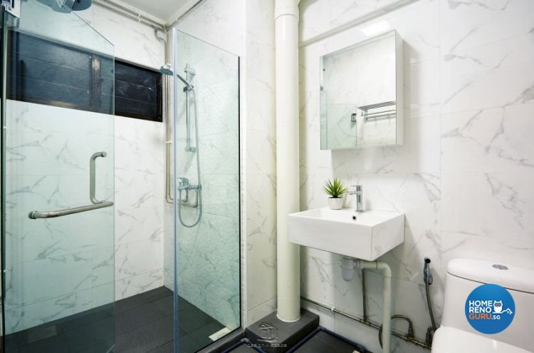 Toilet with a wall-mounted vanity and sink, with glass shower partition